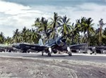 F4U-1A Corsair of Marine Squadron VMF-216 taxis down the strip at Torokina, Bougainville, Solomon Islands, Dec 1943. Note TBM Avengers and NE-1 Grasshoppers parked along the strip.