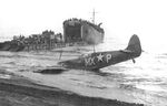 Supermarine Spitfire of the US 307th Fighter Squadron rests on the beach at Paestum, Italy near Salerno after being shot down Sep 9, 1943; pilot uninjured. LST-391 unloads men and materiel beyond, Sep 1943. Photo 1 of 2