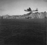 B-24 Liberator of the 98th Bomb Squadron flying past the island of Chi Chi Jima, Japan, 1944-45.