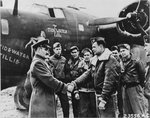 "BGen Westside T Larson, CO of Antisub Command in England, commends Capt Jack H Shaw, Navigator of B-24D Liberator ""Tidewater Tillie,"" at RAF St Eval, Cornwall, England after the aircraft sank a German U-Boat in the Bay of Biscay."