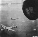 "B-24M Liberator ""Top o' the Mark"" and other bombers of the 23rd Bomb Squadron over Allied invasion fleet at Balikpapan, Borneo, July 2 1945."