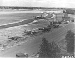 "View of the control tower at RAF Bassingbourn, Cambridgeshire, England, UK, 1945. Note line of 91st Bomb Group ""hack"" aircraft: Piper L-4 Grasshopper, Noordyne O-64 Norseman, P-47 Thunderbolt, and Cessna UC-78 Bobcat."