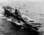 USS Enterprise with wartime camouflage under way with F6F Hellcats and SB2C Helldivers on her flight deck, 1944