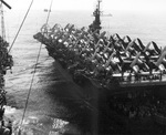 Escort Carrier USS Attu and Fleet Carrier USS Shangri-La (left) exchanging personnel and equipment by high wire while at sea, 3 Sep 1945. Note F4U Corsairs and SB2C Helldiver aircraft on Attu's deck.