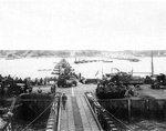 Military vehicles move ashore from Mulberry Artificial Harbor A, across a pontoon bridge, to Omaha Beach, Normandy, France, June 16 1944 (D+10). Visible are M3 Halftracks, an M8 Greyhound, and AFKWX 2½-ton Trucks.