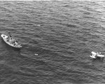 OS2U Kingfisher floats on the ocean near a US Coast Guard cutter as they rescue survivors of a merchant ship torpedoed off the US East Coast; photograph from a US Navy airship, 1942