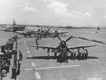 P-47D Thunderbolts of the 318th Fighter Group are loaded onto Escort Carrier USS Natoma Bay, Pearl Harbor, Hawaii, June 1, 1944. The Fighter Group was on its way to Saipan, Marianas. Note USS Manila Bay with the rest of the Fighter Group's Thunderbolts.