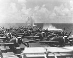 "P-47D Thunderbolts of the 318th Fighter Group being ferried to Saipan on Escort Carrier USS Manila Bay. Note bomb splashes from an aerial attack by four D3A Aichi ""Val"" dive bombers during refueling operations east of Saipan, Jun 23 1944. Photo 1 of 2"