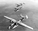Two PBM-1 (front) and two PBM-3 (back) in flight, 1942. The PBM-1s are from an early production series with retractable floats that were discontinued for principal production. Location unknown. Photo 2 of 2