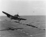 SB2C Helldiver getting a wave-off from USS Bunker Hill, 1943. Note Helldiver in the distance with wheels up but flaps down, apparently preparing for a water landing.
