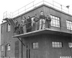 The 401st Bomb Group's control tower at RAF Deenethorpe, Northamptonshire, England, UK, Feb 26 1945. Note a US Navy Captain among the group of observers.