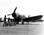 "Ground crewmen arming an FG-1D Corsair of Marine Fighting Squadron 312, the ""Checkerboarders,"" at Kadena airfield, Okinawa, Japan, Apr-Aug 1945"