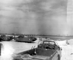 DUKWs on the beach at Selsey, West Sussex, England prior to the Normandy invasion, May 1944. Note components of the artificial Mulberry Harbors in the background awaiting deployment.