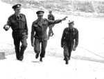 Canadian officers enter Château de Rots, Normandy, France. Left to right they are Colonel Richard S Malone, Lt General Henry Crerar (Commander, 1st Canadian Army) and Major Austin.