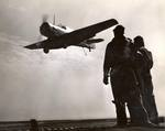 Landing Signal Officers stand-by as an SNJ Texan approaches training aircraft carrier USS Sable for a landing on Lake Michigan, United States, 1943.
