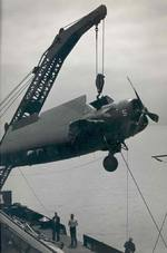 A damaged FM-2 Wildcat being hoisted by a crane from the training aircraft carrier USS Sable to a waiting barge on Lake Michigan, United States, 1943-45.