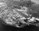 Aerial view of Hickam Field looking toward Honolulu, Hawaii, 3 May 1940. The Pearl Harbor entrance channel is along the bottom of the photo and the Submarine Base can be seen at the upper left.
