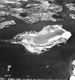 Ford Island, Pearl Harbor shipyard, and Hickam Field, Oahu, Hawaii post-war, Aug 4, 1951. Note oil slick streaming from the sunken Arizona, upper left.