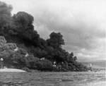 Black smoke pours from fuel oil fires on Battleship Row, Dec 7, 1941. Capsized Oklahoma at left with masts of Maryland, Tennessee, West Virginia, and Arizona in Pearl Harbor, Oahu, Hawaii.