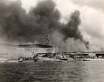 Damaged PBY Catalinas on the seaplane ramp of Ford Island, Pearl Harbor, Oahu, Hawaii, Dec 7, 1941. White smoke from burning hangars and black smoke from burning battleships is also visible.