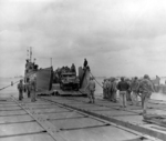 LCT-525 delivering a half-track onto a pontoon causeway pier at Utah Beach, Normandy, France, Jun 15 1944.  Half track is an M16 Anti-Aircraft gun mount of A Co, 376th AAA Battalion.