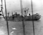 Liberty ship unloading two CCKW trucks and other supplies onto a Rhino cargo barge off the Normandy beaches, Jun 1944.