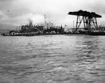 USS Oglala capsized at the 1010 Dock, Pearl Harbor, Oahu, Hawaii, Dec 8, 1941. USS Argonne is on the left beyond the dock and Floating Crane YD-25 on the right.