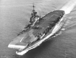 Aircraft carrier HMS Illustrious underway, 1942.  A Swordfish torpedo plane is on the flight deck and an admiralty disruptive camouflage scheme also extends across the flight deck.