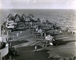 "F6F-5 Hellcats of Air Group 11, the ""Sundowners,"" warm up on the deck of USS Hornet (Essex-class) in the Philippine Sea, late 1944"