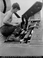 Marine Pfc C.H. McClure servicing the three Browning M2 .50 caliber machine guns in the right wing of an F4U-1 Corsair fighter on Bougainville, Dec 9, 1943