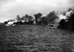 Escort Carrier USS Gambier Bay, Destroyer Escort USS Raymond, and another Destroyer Escort, elements of Taffy 3, laying smoke before engaging the Japanese Center Force in the Battle Off Samar, Oct 25, 1944.