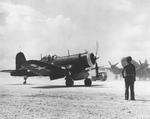 F4U-1 Corsair of Marine Squadron VMF-114 set for take-off from Peleliu, late 1944. Note C-46 Commando.