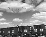 WC-54 ambulances at RAF Kimbolton, England waiting as returning B-17 Fortress bombers of the 379th Bomb Group fly overhead, May 13, 1944