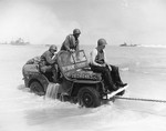 An amphibious Jeep being towed ashore at Normandy, France, Jun 12, 1944. Note that censors have deleted markings on the Jeep