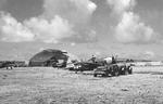 P-47 Thunderbolts of the 19th Fighter Squadron share the airfield with Marine Corps TBM Avengers Isely Field on Saipan, Mariana Islands, mid 1944. Note incomplete Japanese hangar.