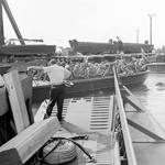 Andrew Higgins standing on the bow ramp of an LCVP prototype observing an exercise with a loaded Eureka Boat (predecessor of the LCP(L)), New Orleans, Louisiana, United States, circa 1941. Note other boats on the wharf.