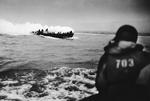 LCVP landing craft from Amphibious Transport Ship USS Samuel Chase approaching Omaha Beach. The boat is smoking from a fire that resulted when a German machine gun bullet hit a soldier's hand grenade.