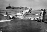 Supermarine Spitfire of the US 307th Fighter Squadron rests on the beach at Paestum, Italy near Salerno after being shot down Sep 9, 1943; pilot uninjured. LST-359 unloads men and materiel beyond, Sep 1943. Photo 2 of 2