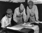 LtCol LF Maybach, with pen, completing paperwork relating to Japanese POW 2Lt Minoru Wada, seated, Aug 7, 1945, Libby Field, Davao, Mindanao, Philippines.