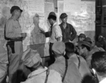 US Army Ground Liaison Officer Maj Mortimer Jordan, left, Japanese POW 2Lt Minoru Wada, center, and interpreter Sgt Charles Imai provide a briefing for fighter and bomber pilots of the 1st Marine Air Wing, Aug 9, 1945