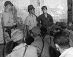 US Army Ground Liaison Officer Maj Mortimer H Jordan, left, Japanese POW 2Lt Minoru Wada, center, and interpreter Sgt Charles T Imai provide a briefing for the 1st Marine Air Wing fighter and bomber pilots, Aug 9, 1945