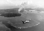 Smoke rising from Colonia Harbor on Yap, Caroline Islands as a TBM Avenger from the carrier Yorktown (Essex-class) flies overhead, 25-28 July 1944