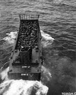 An LCM (Landing Craft Mechanized) loaded with troops shoves off from the troop transport and heads toward the shore at Iwo Jima, Mar 6, 1945.