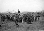 Marines and Army ground crews look over the first Sikorsky R-4 helicopter to land in the fighter strip on Iwo Jima, Mar 23, 1945.