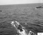 After being abandoned by her crew, an American boarding party comes alongside the damaged German U-505 off the West African coast, 4 Jun 1944. Destroyer Escort USS Chatelain circles the capture.