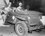 Stars and Stripes correspondent and cartoonist Bill Mauldin at the wheel of his assigned Jeep accompanied by fellow illustrator Gregor Duncan, Naples, Italy, Mar 1944