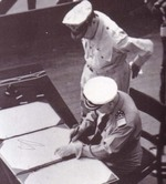 Admiral Conrad E. L. Helfrich signing the Japanese surrender document on behalf of the Netherlands aboard USS Missouri, 2 Sep 1945; note MacArthur next to Helfrich. Photo 2 of 2.