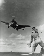 "USS Yorktown (Essex-class) Landing Signal Officer Lt Richard C Tripp giving the ""cut"" signal to the pilot of a landing F6F Hellcat fighter, Pacific Ocean, 1944."