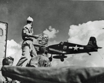 USS Yorktown (Essex-class) Landing Signal Officer Lt Richard C Tripp watching the landing of an F6F Hellcat fighter, Pacific Ocean, 1944.
