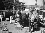 Royal Australian Navy personnel examining the hulls and pieces of the Japanese Type A midget submarines recovered from Sydney Harbor after the 31 May 1942 raid.